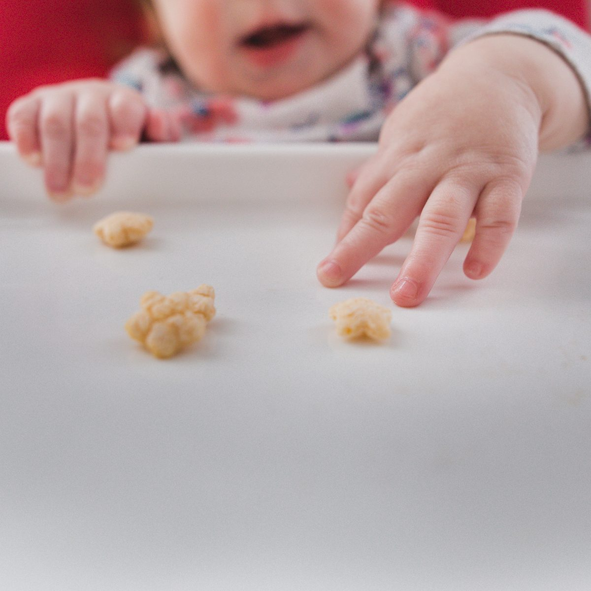 Baby girl sitting in high chair reaching for a cereal puff