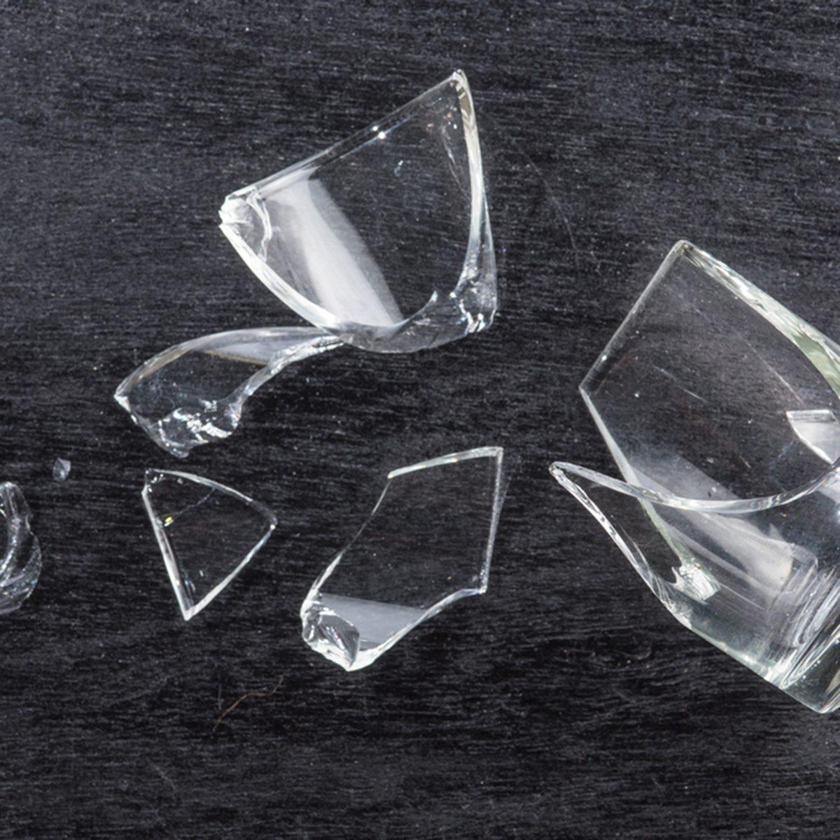 broken glass on dark wood background, concept of danger