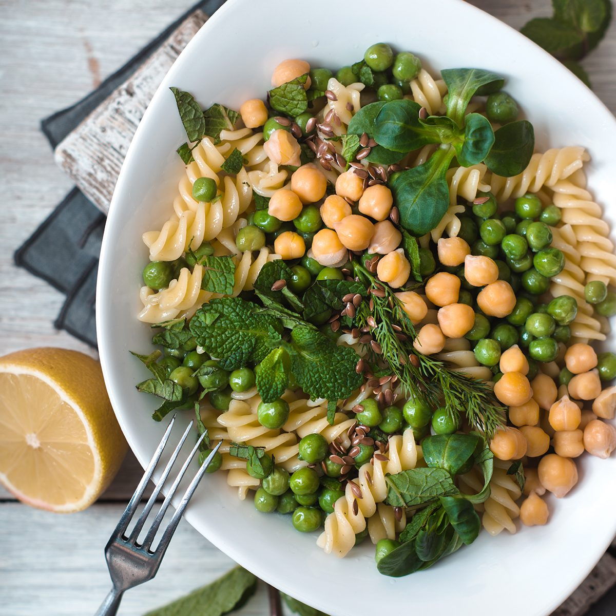 Salad with fusilli, chickpeas, grass in a white ceramic bow
