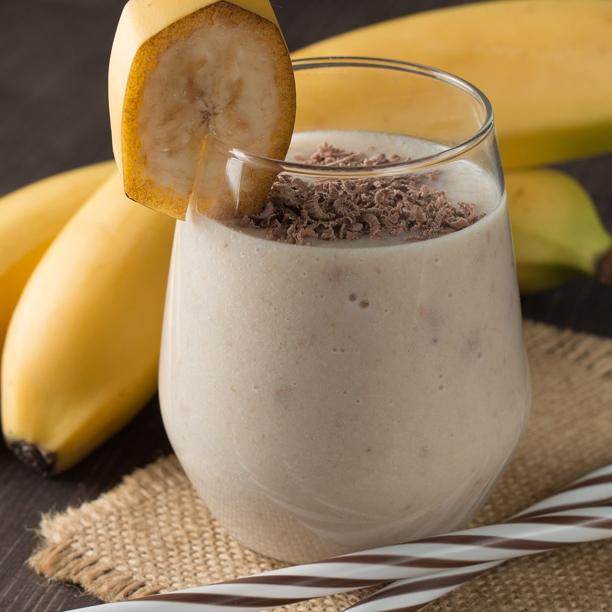Photo of fresh Made Chocolate Banana Smoothie on a wooden table with coffee and spices.