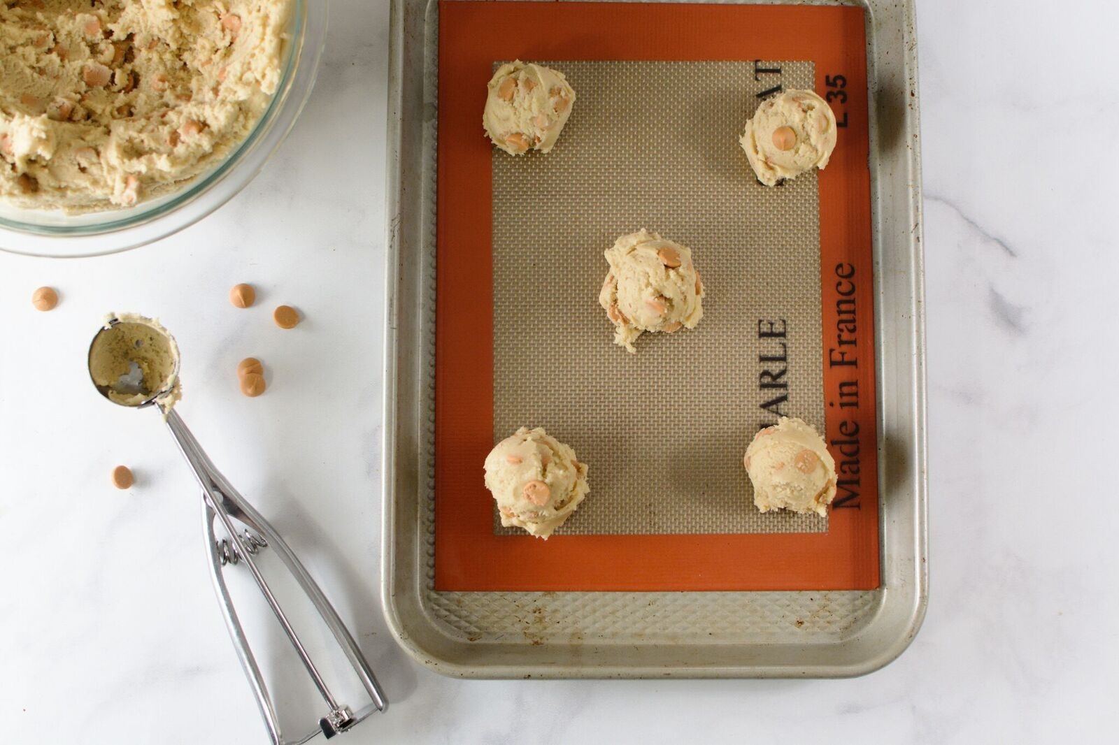 Cookie dough drops on a baking sheet