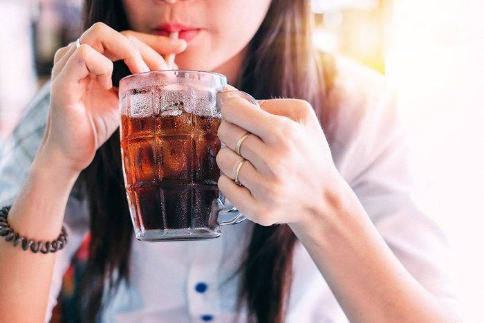 closeup woman drinking ice cola in the glass.food and beverage concept