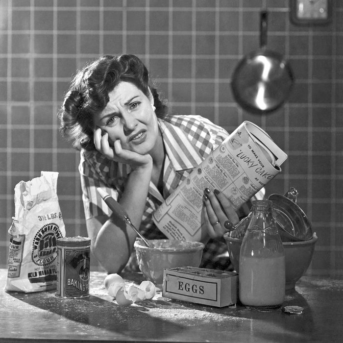 A frustrated woman with a mess in her kitchen from trying to bake a cake. It was an early ad for Bisquick.