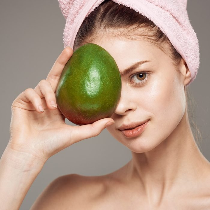 woman with green fruit, mango, clean skin, hair mask