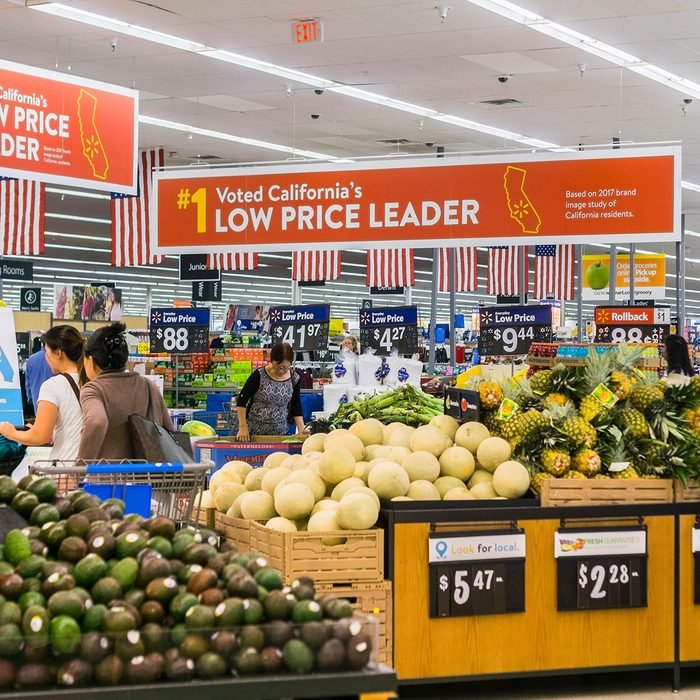 People shopping in the food and vegetable area of one of Walmart's stores in south San Francisco bay area; Banners advertising the low price leader status