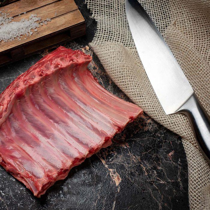 Raw ribs beside a knife