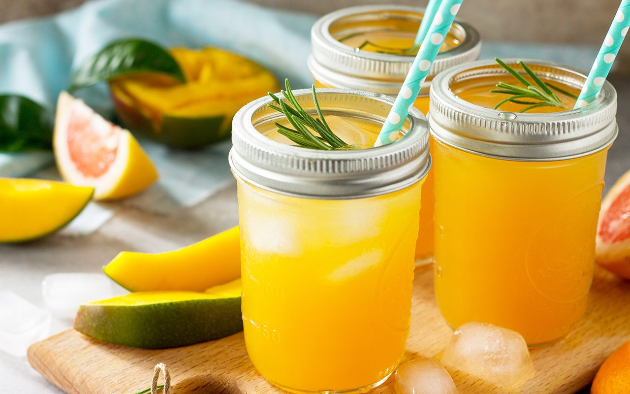 Refreshing summer cocktails made of citrus and mango, cold drink or a drink with ice on a black background.