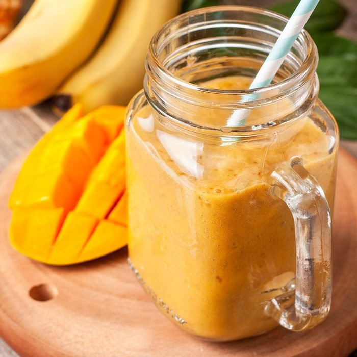 smoothie with tropical fruits: mango, banana, pineapple in a glass jar Mason on the old wooden background
