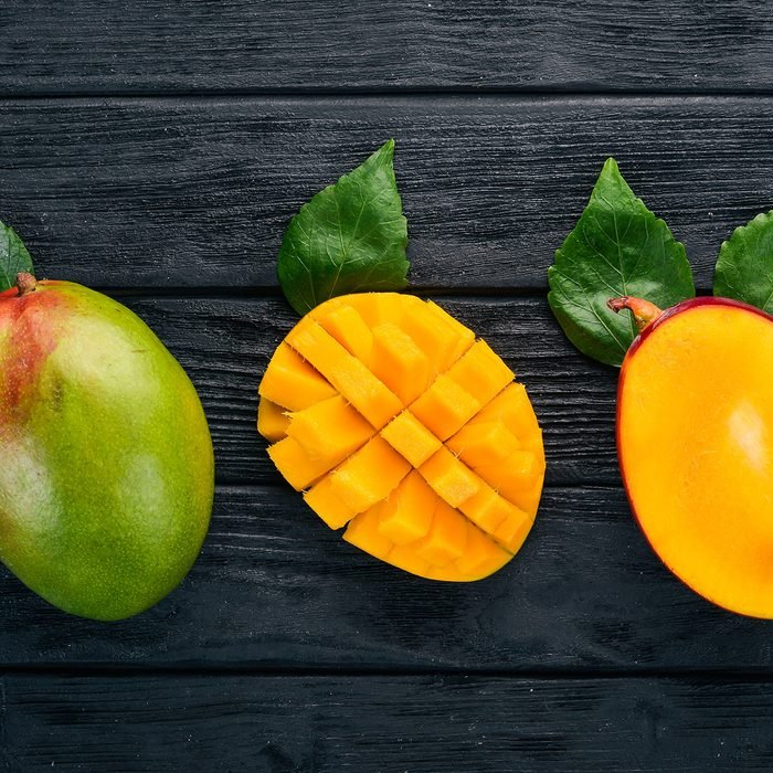 Mango. Tropical Fruits. On a wooden background.