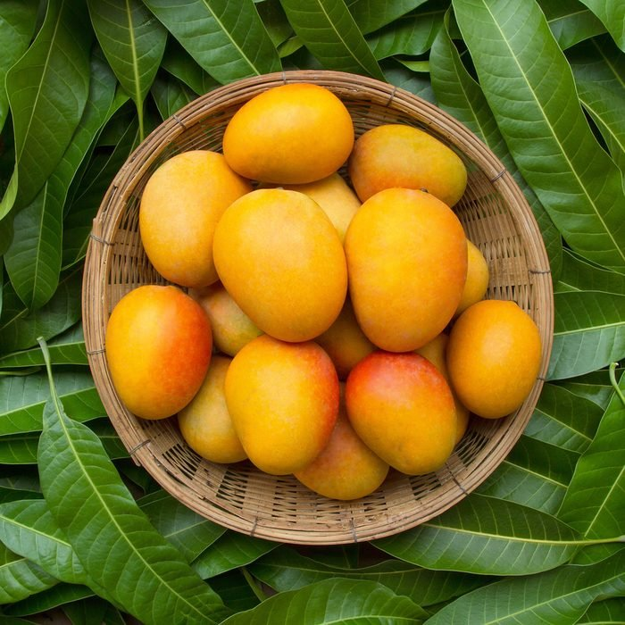 Mango tropical fruit in wooden basket put on green leaf background, top view