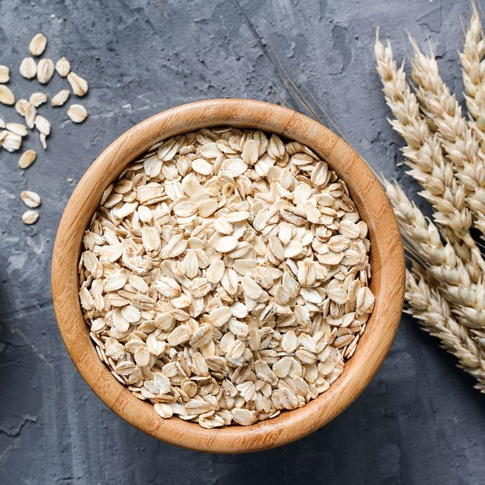 Rolled oats or oat flakes in wooden bowl and golden wheat ears on stone background.