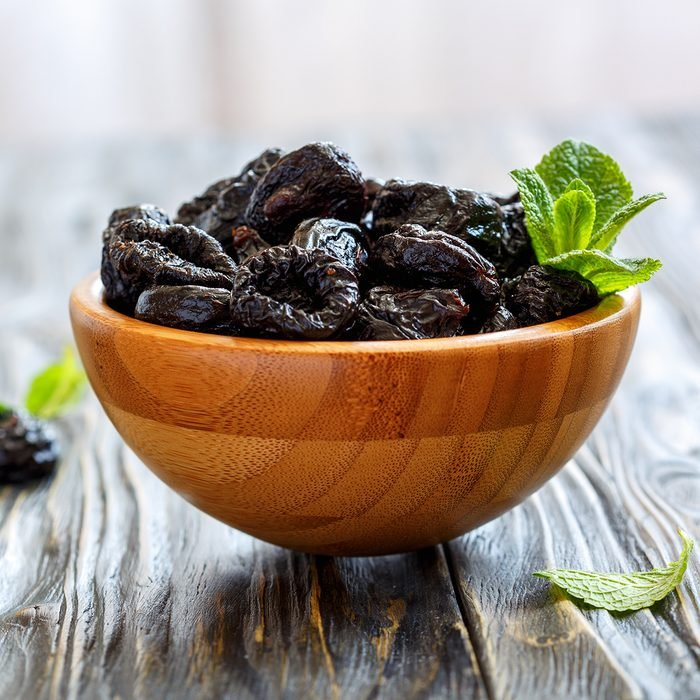 Prunes and mint in a bowl on old wooden table, selective focus.