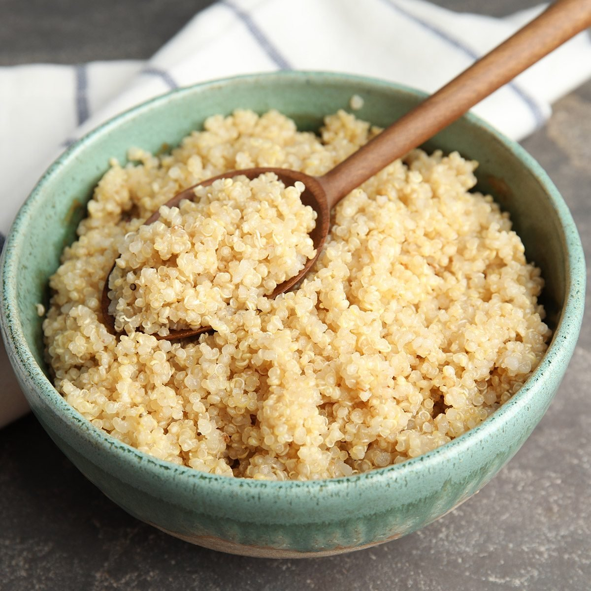 Composition with cooked quinoa in bowl and wooden spoon on table