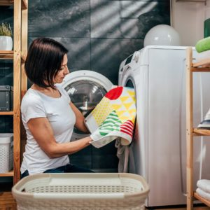 Women checking her laundry as she removes them from the washing machine.; Shutterstock ID 1060298948; Job (TFH, TOH, RD, BNB, CWM, CM): Taste of Home