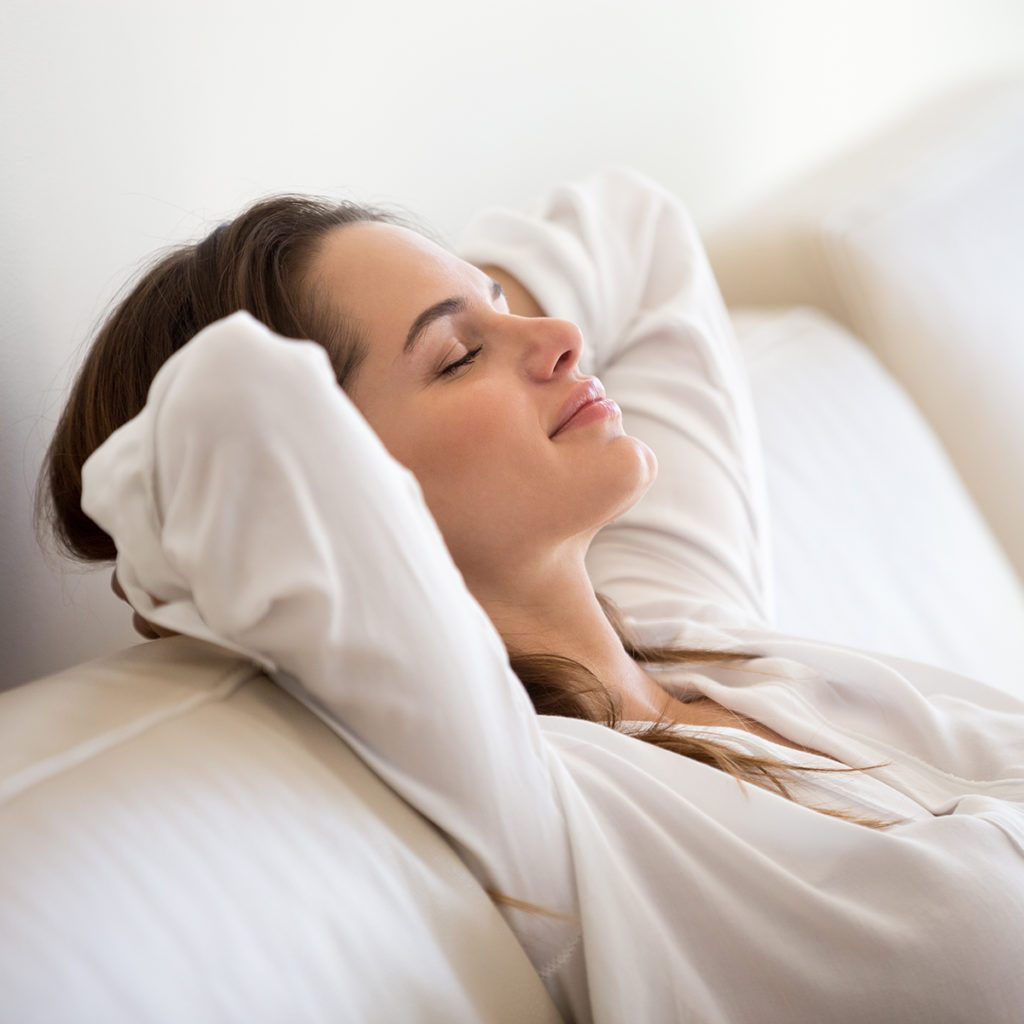Calm millennial woman relaxing on soft comfortable sofa meditating or having daytime nap, carefree lazy girl breathing fresh air enjoying no stress free peaceful weekend morning resting on couch; Shutterstock ID 1126189856; Job (TFH, TOH, RD, BNB, CWM, CM): Taste of Home