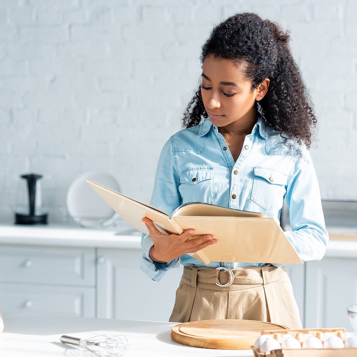 attractive african american woman reading cookbook in kitchen; Shutterstock ID 1229629288; Job (TFH, TOH, RD, BNB, CWM, CM): TOH
