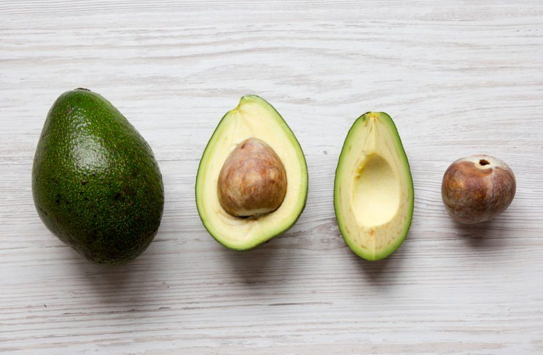 Whole and chopped avocados on white wooden background, overhead view. Top view, from above, flat lay.