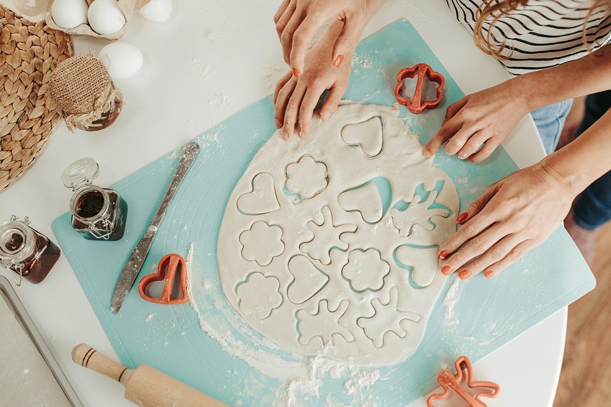 Top view photo of the dough and lovely shaped cookie cutters. Hands of woman and girl on the table; Shutterstock ID 1341039155; Job (TFH, TOH, RD, BNB, CWM, CM): TOH