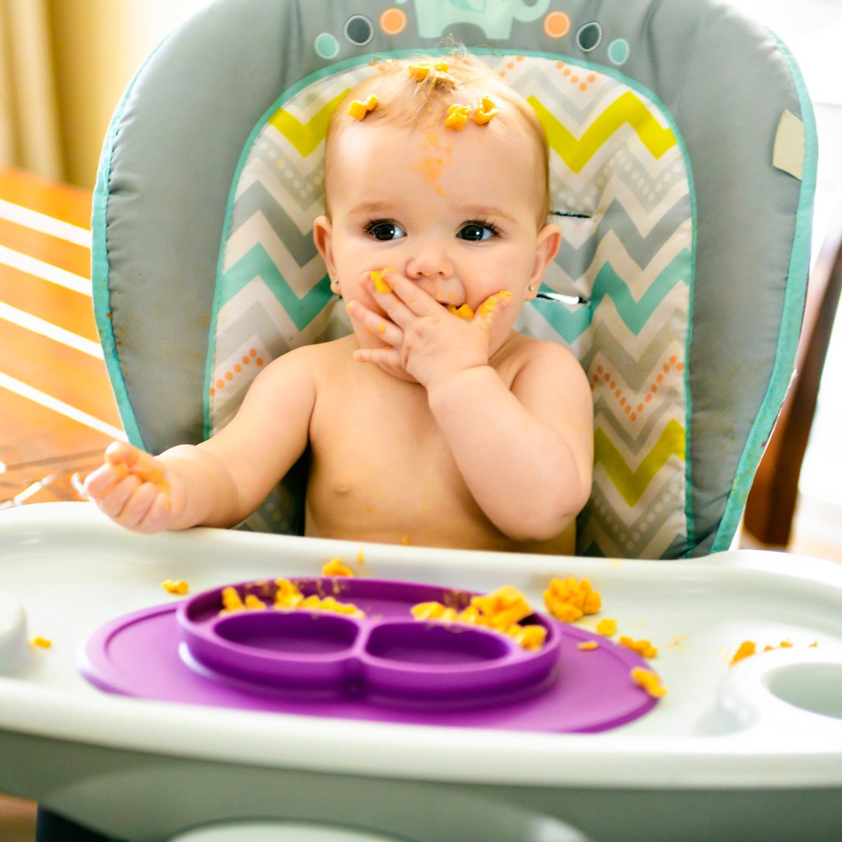 Little baby eating her pasta and making a mess
