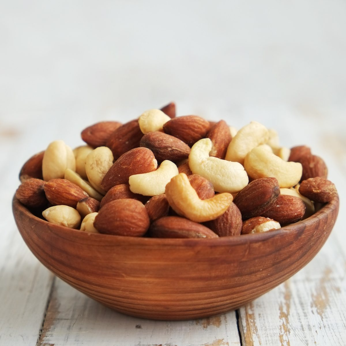 Mixed nuts in a bowl on a white wooden background.