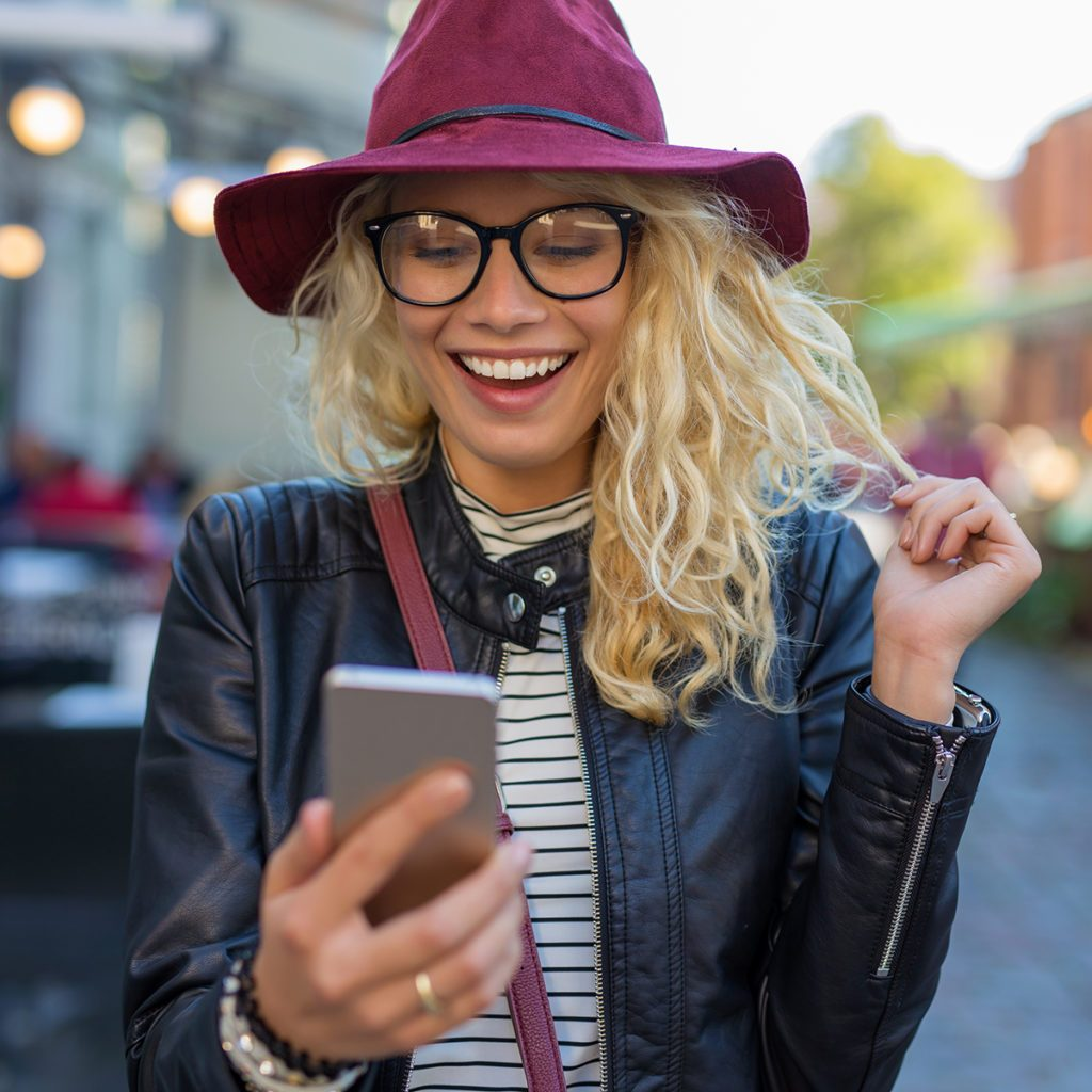 Happy and funny woman looking at her phone; Shutterstock ID 518846440