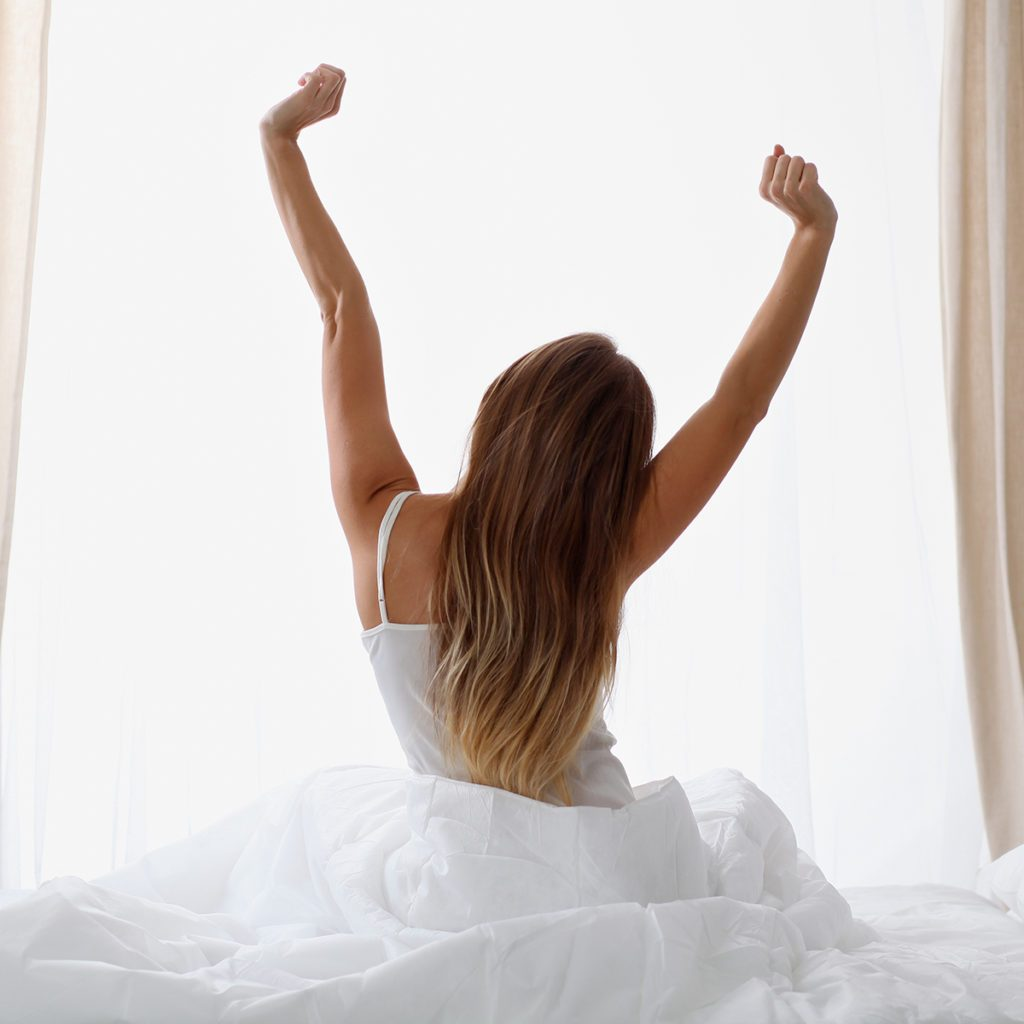 Woman stretching in bed after waking up, back view, entering a day happy and relaxed after good night sleep. Sweet dreams, good morning, new day, weekend, holidays concept; Shutterstock ID 578356282; Job (TFH, TOH, RD, BNB, CWM, CM): Taste of Home