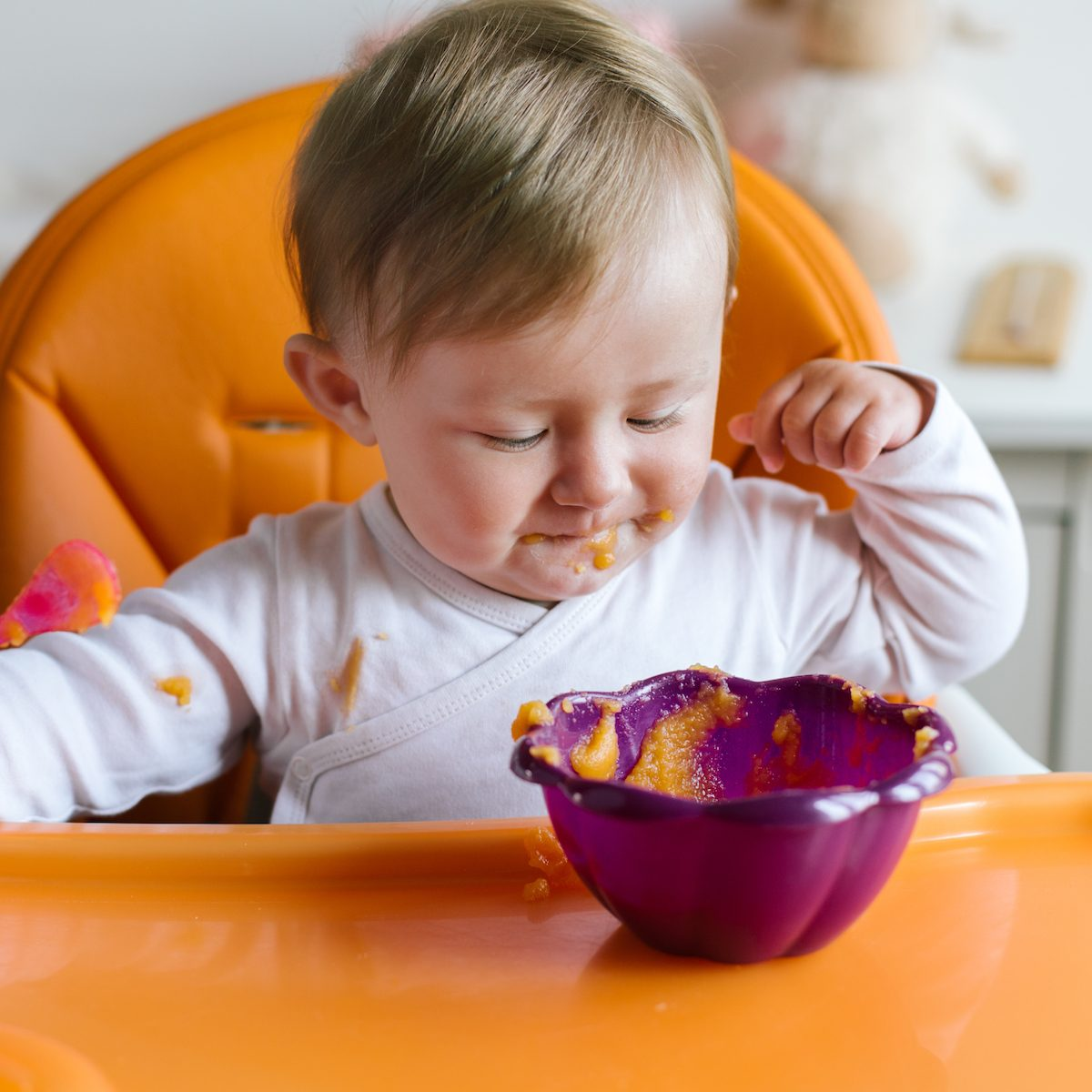 Portrait of baby girl sitting in high chair and eating sweet potato