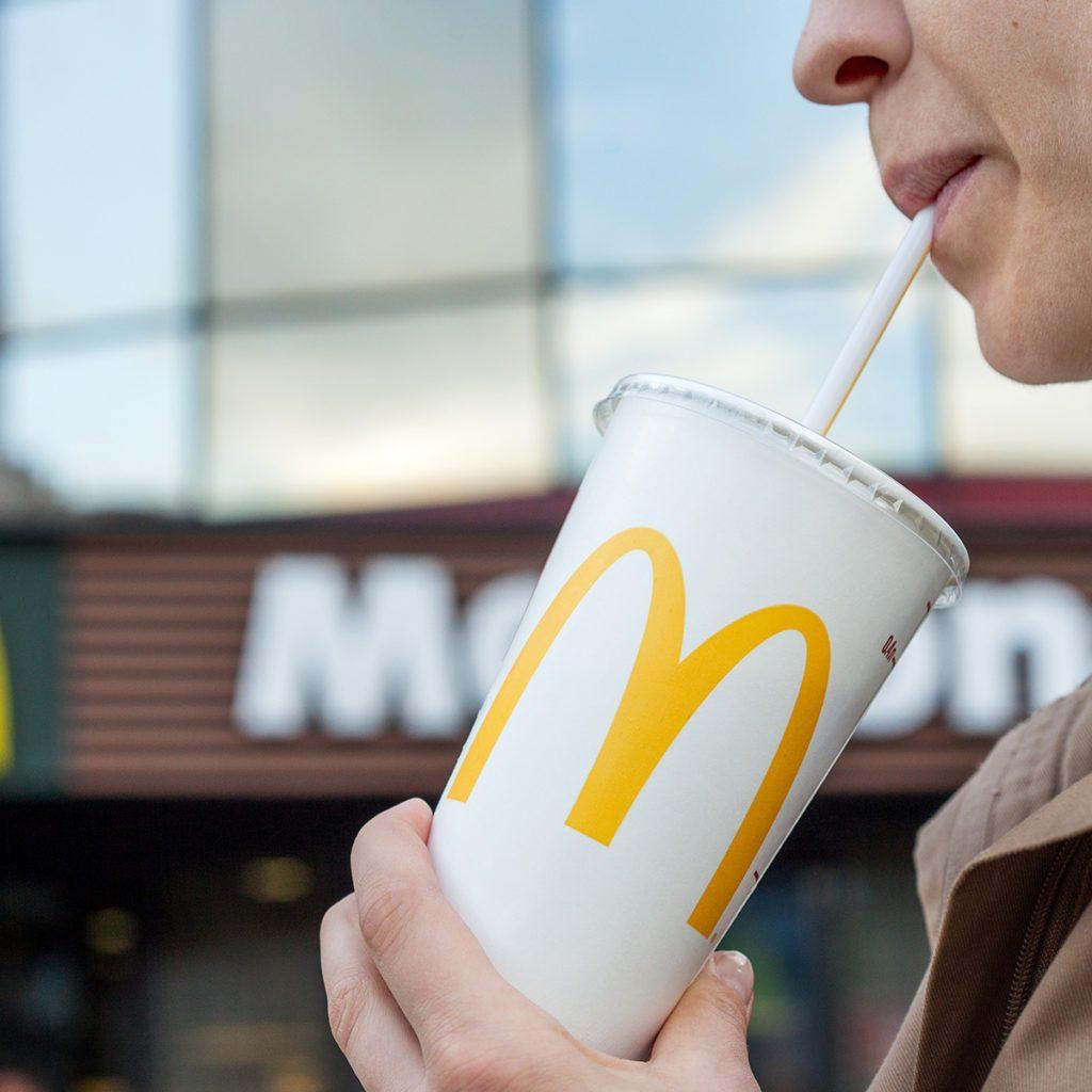 Minsk, Belarus, june 23, 2017: McDonald's soft drink. Woman drinks a drink in the background of the McDonald's restaurant; Shutterstock ID 670136818