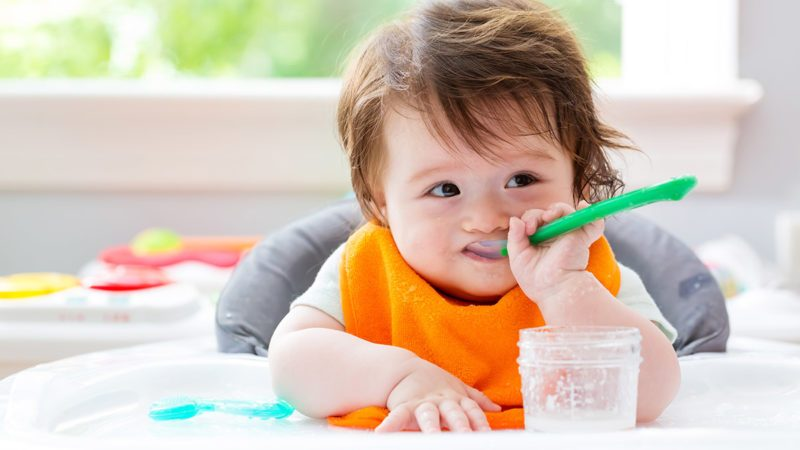 Happy little baby boy eating food with a spoon; Shutterstock ID 673709560; Job (TFH, TOH, RD, BNB, CWM, CM): Taste of Home