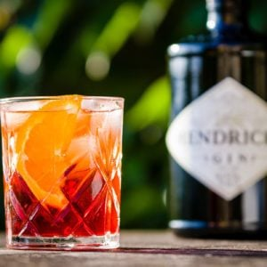 DRAZOVICE - JUNE 24: Negroni cocktail in crystal cut glass and a bottle of gin on June 24, 2016 in Drazovice, Czech Republic. The cocktail is made of gin, sweet vermouth, and Campari.; Shutterstock ID 693339346; Job (TFH, TOH, RD, BNB, CWM, CM): TOH