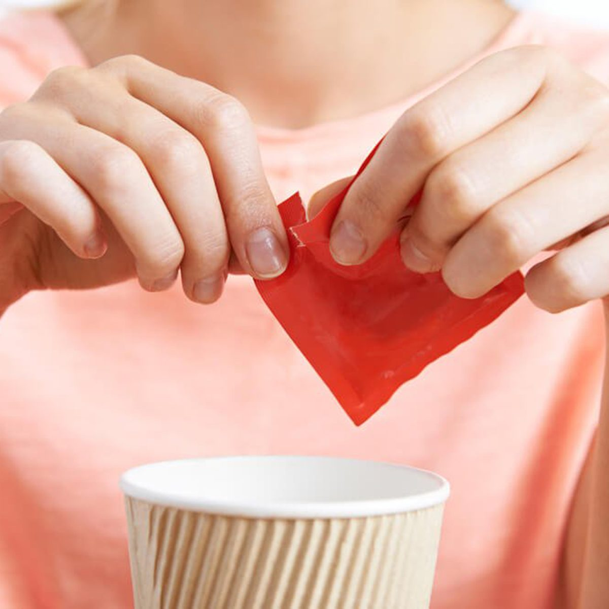 Emptying a sweetener packet into a coffee