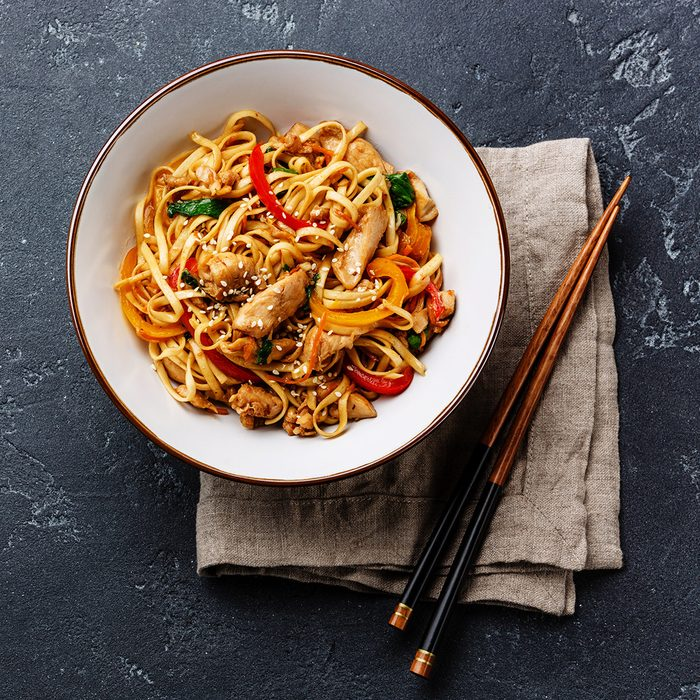 Udon stir-fry noodles with chicken meat and sesame in bowl on dark stone background