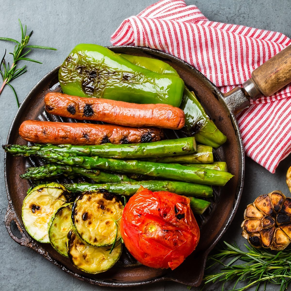 Grilled sausages and green vegetables - zucchini, asparagus, bell pepper, garlic, lemon and rosemary on cast iron grill pan.
