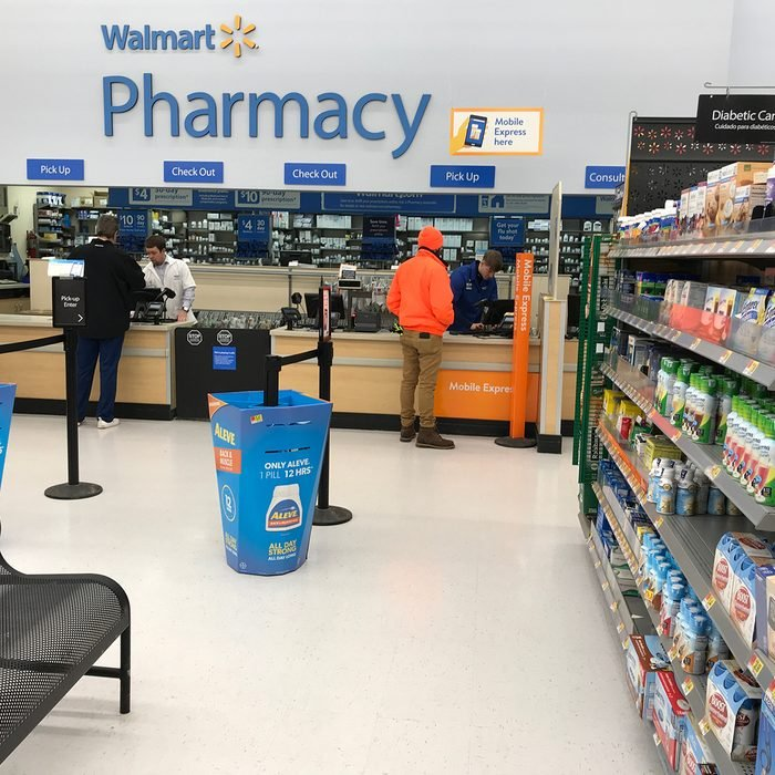 Two customers pick up their orders at a Walmart pharmacy in Minnesota.