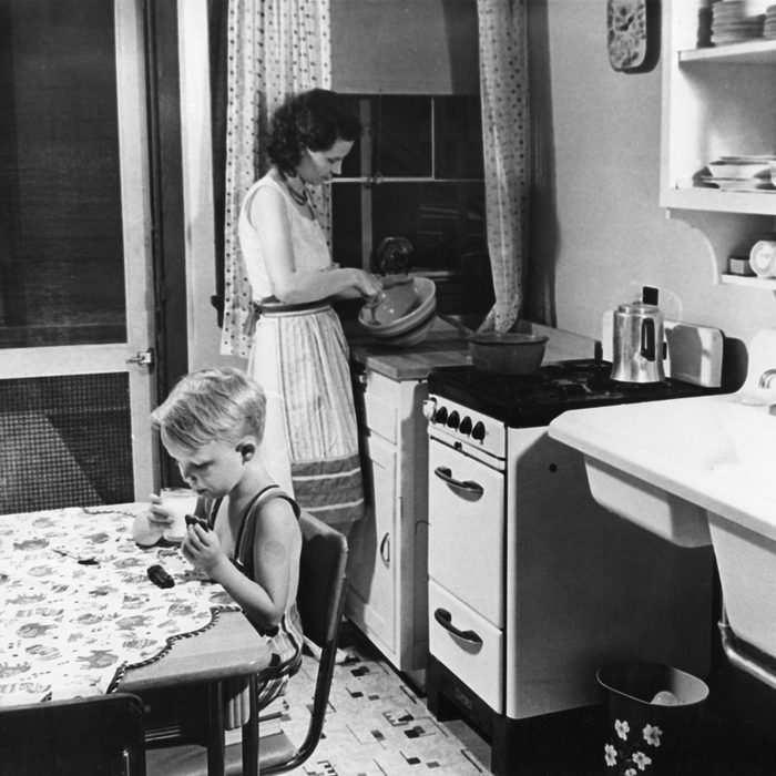 Woman Cooking in Kitchen with Young Boy Eating Cookies with Milk
