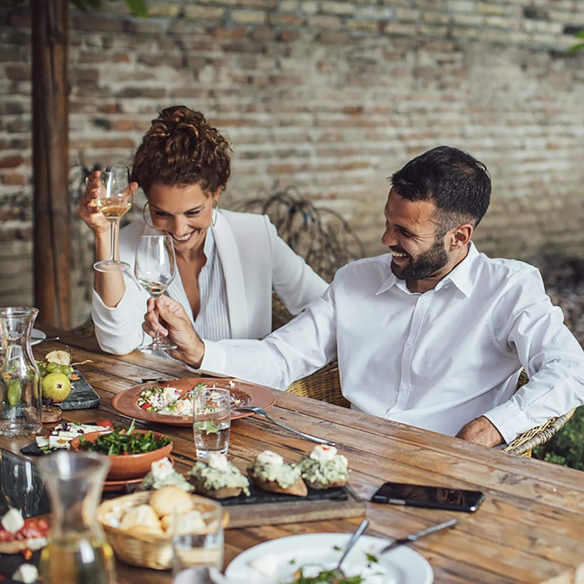 Beautiful Caucasian smiling couple sitting at restaurant and looking happy.