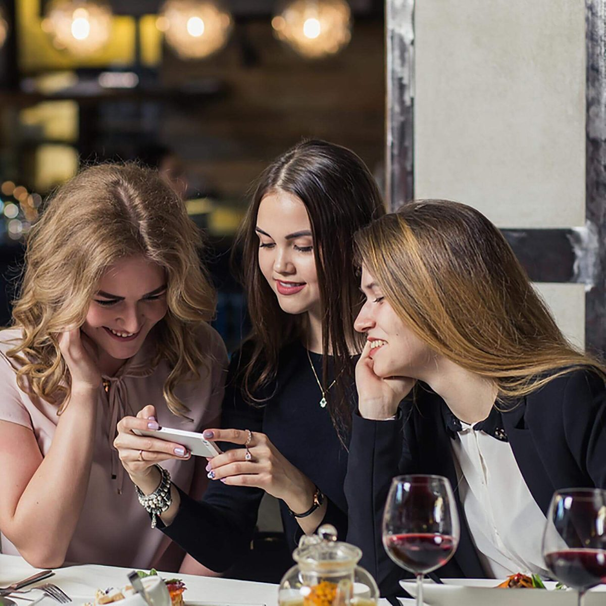 Girls looking at a phone together over food