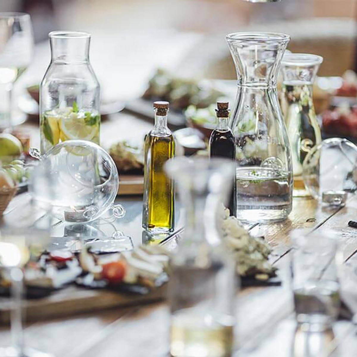 Table spread including olive oil, glasses of water, and appetizers