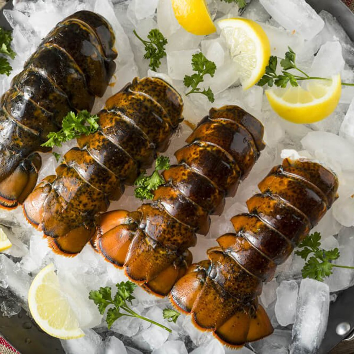 Lobster tails and lemons on ice