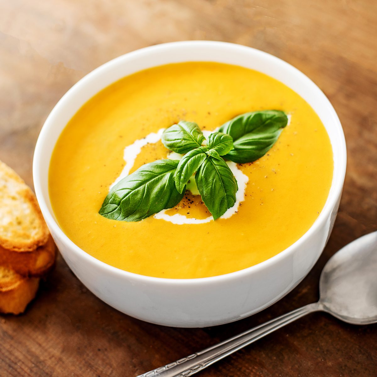 Bowl of squash soup with basil leaf on wood table.