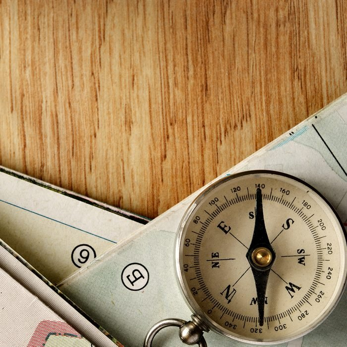 Close up Vintage Compass Instrument on Top of a Wooden Table with Folded Maps