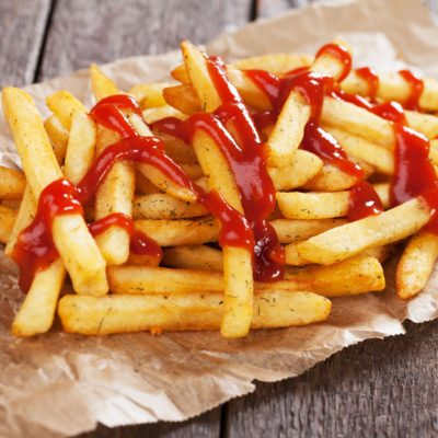 French fries with ketchup served on parchment paper