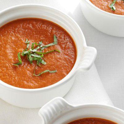 vegan tomato soup recipe in a bowl with basil garnish