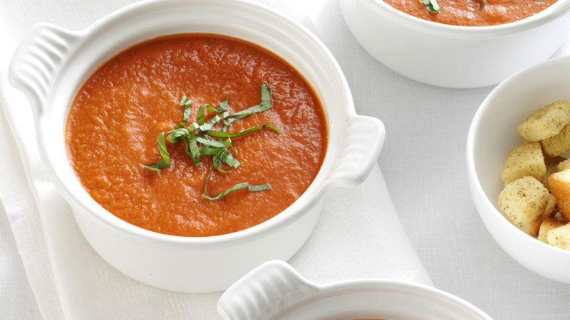 vegan tomato soup recipe in a bowl with basil garnish