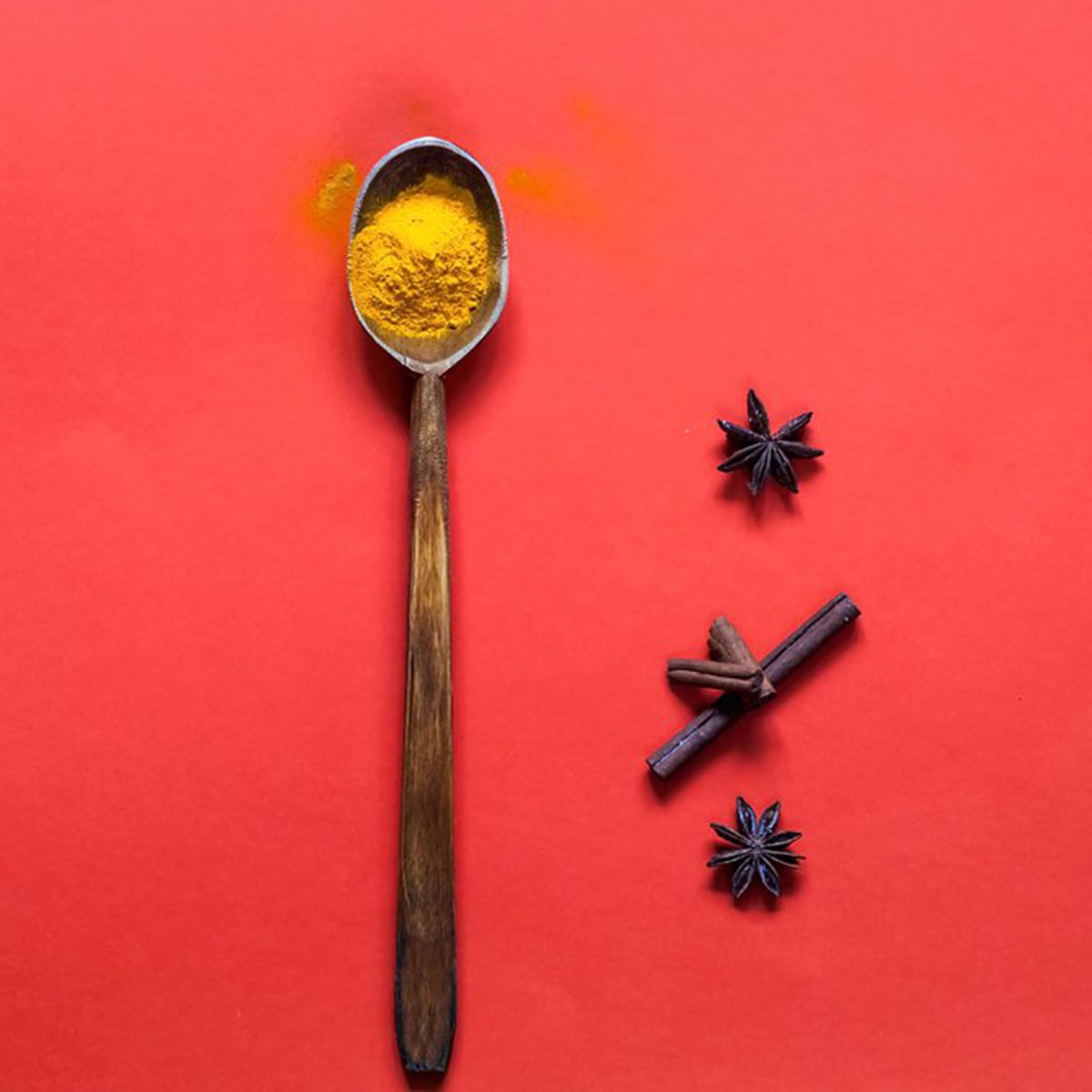 Turmeric in a spoon and star anise on the side against a red background