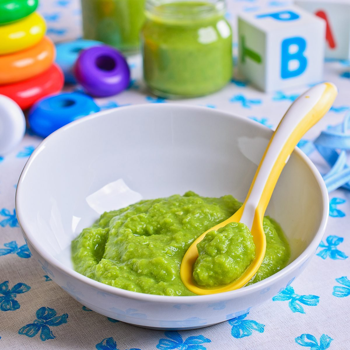 Puree of green in the small bowl is on the background of childrens toys
