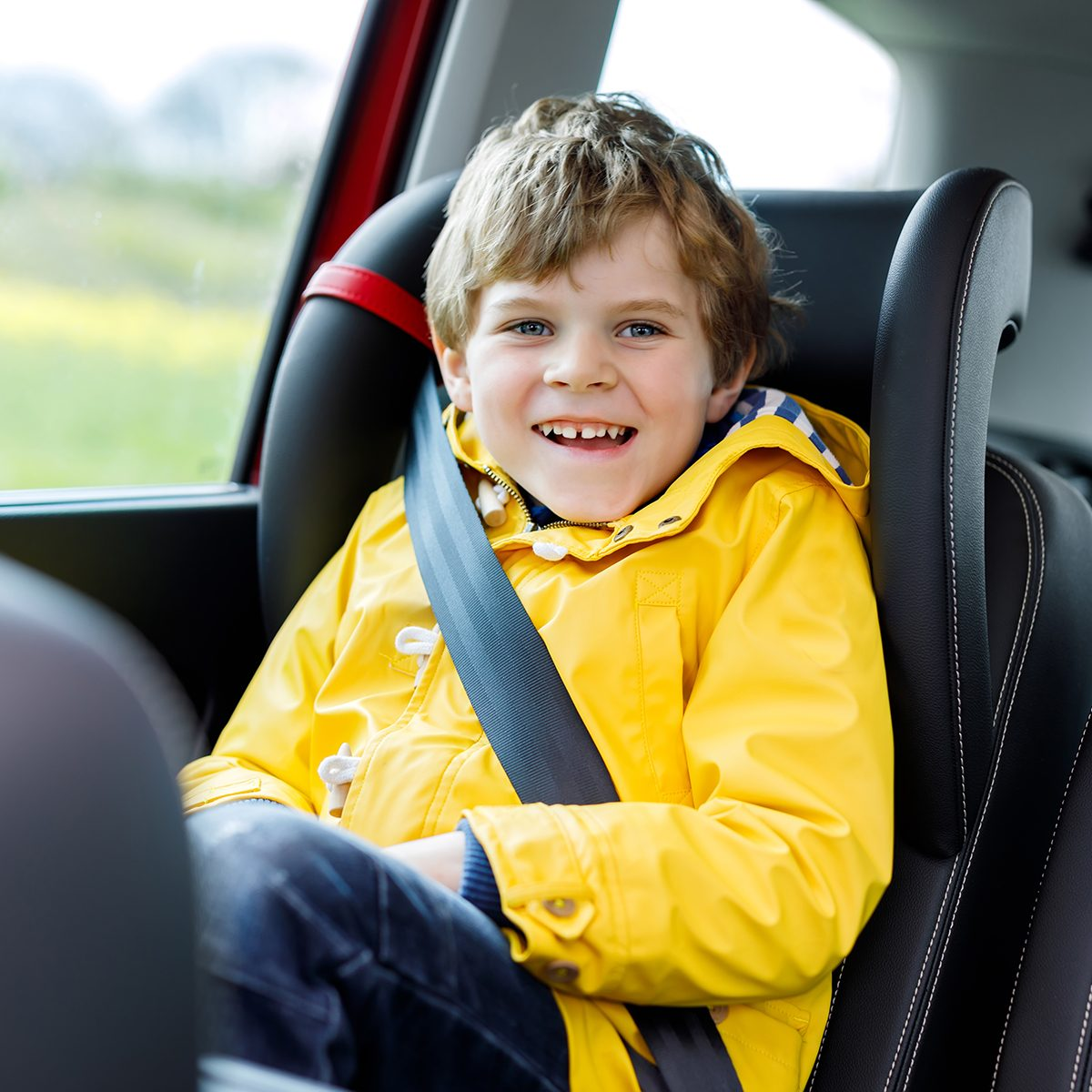 Adorable cute preschool kid boy sitting in car in yellow rain coat.