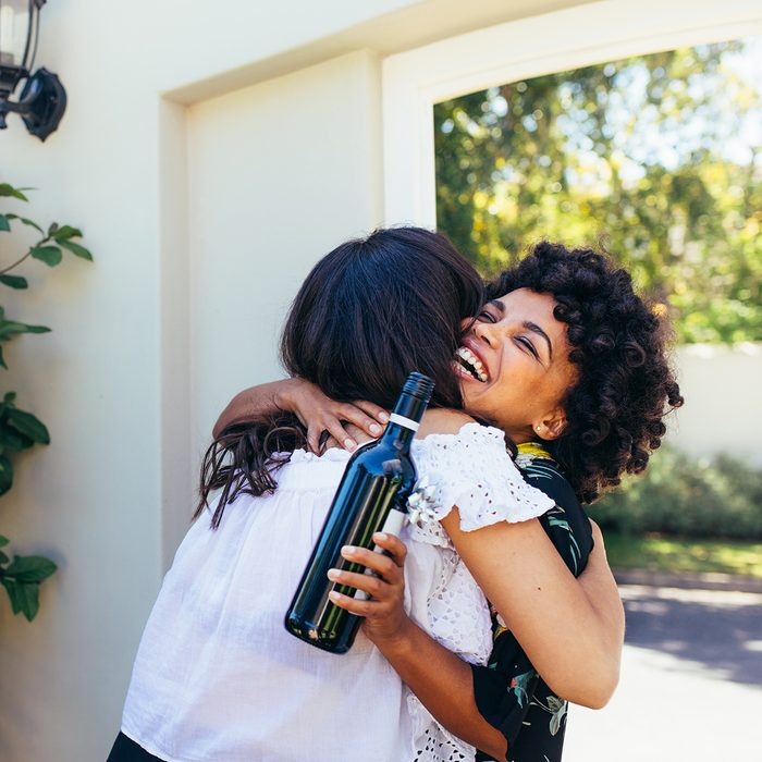 African woman greeting and embracing female friend for having a new house.