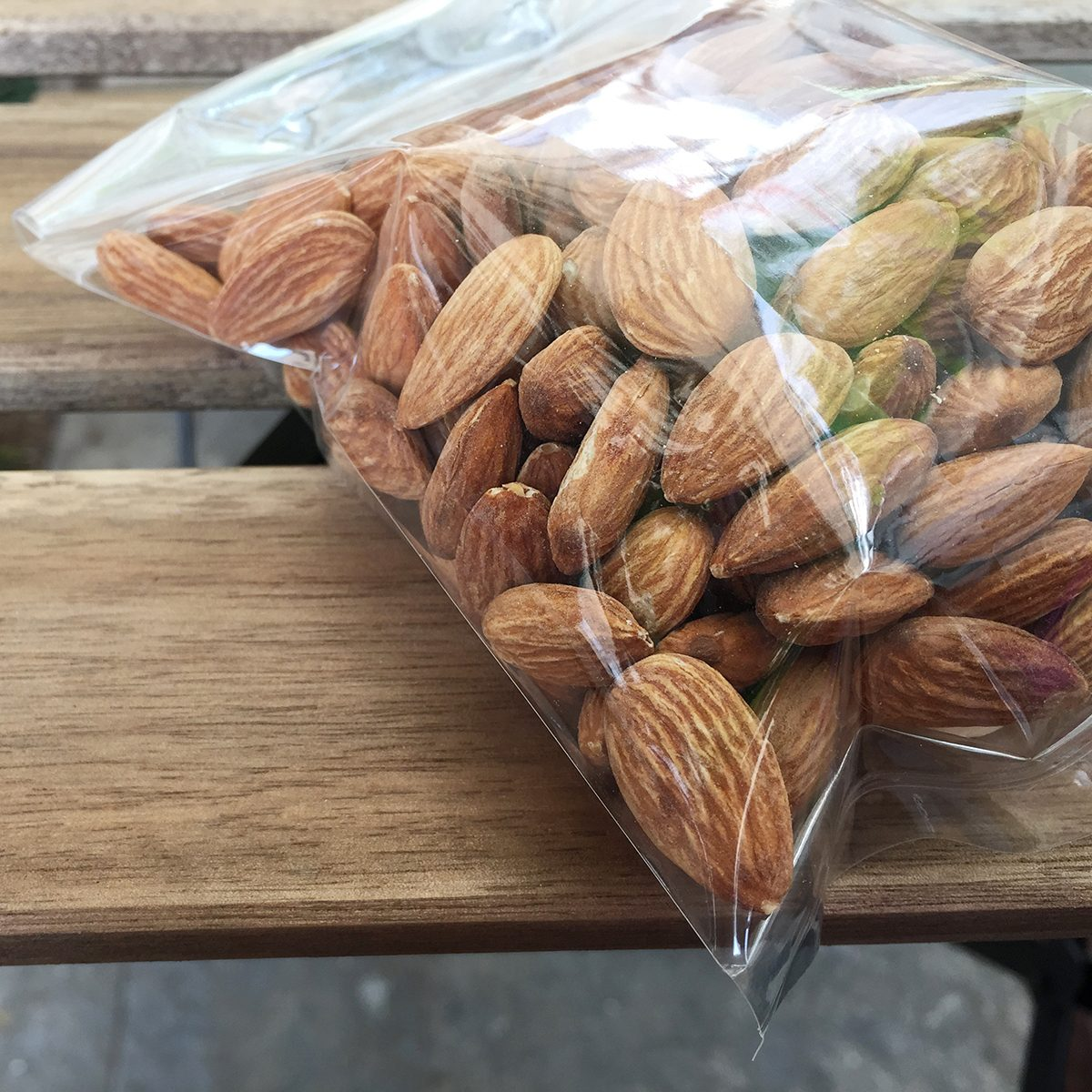 Almond nuts in plastic bag on wood background;