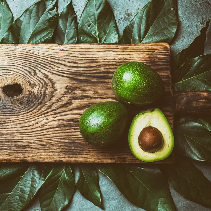Food background with fresh avocado, avocado tree leaves and wooden cutting board.